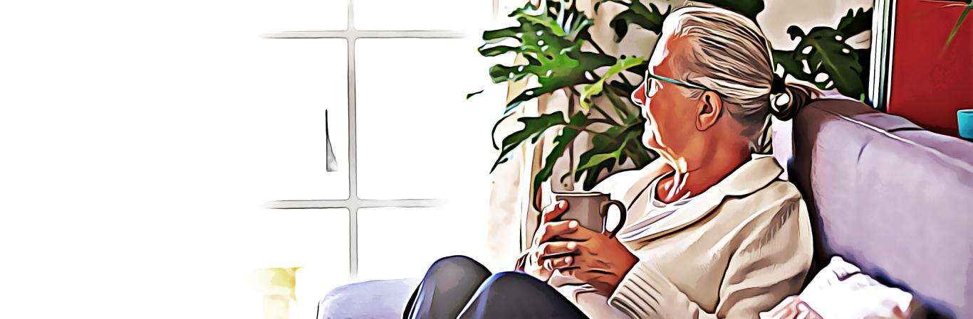 Senior woman holding mug while staring out the window